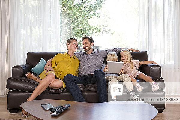 Familie sitzt zu Hause auf der Couch mit Tablette
