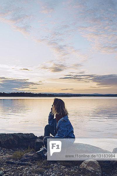 Junge Frau sitzt am Inari-See und schaut auf Aussicht  Finnland