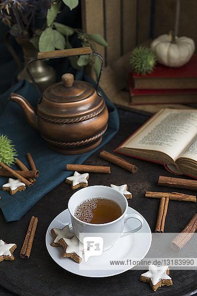 Herbstliches Stilleben mit Tasse Tee und Zimtsternen