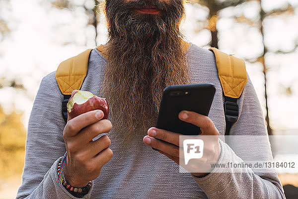 Close-up of bearded man using cell phone and eating an apple on a hiking trip in a forest