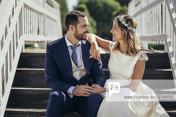 Happy bridal couple sitting on stairs holding hands