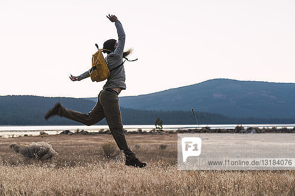 USA  North California  young man on a hiking trip jumping near Lassen Volcanic National Park