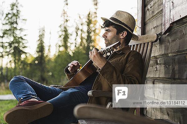 Junger Mann sitzt auf der Veranda eines Holzhauses und spielt Ukulele
