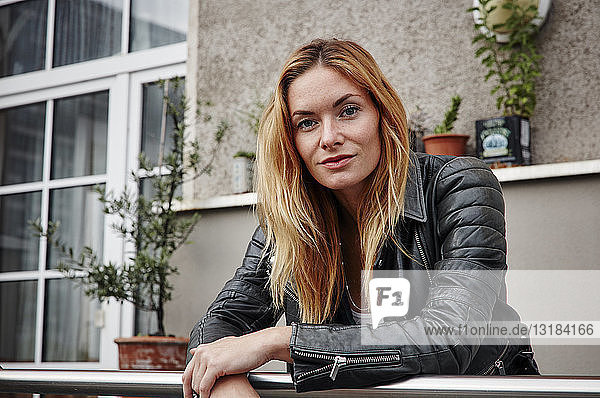Portrait of confident young woman wearing biker jacket leaning on balcony railing