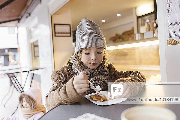 Belgien  Porträt eines Jungen  der im Winter im Freien belgische Waffeln mit Schlagsahne isst