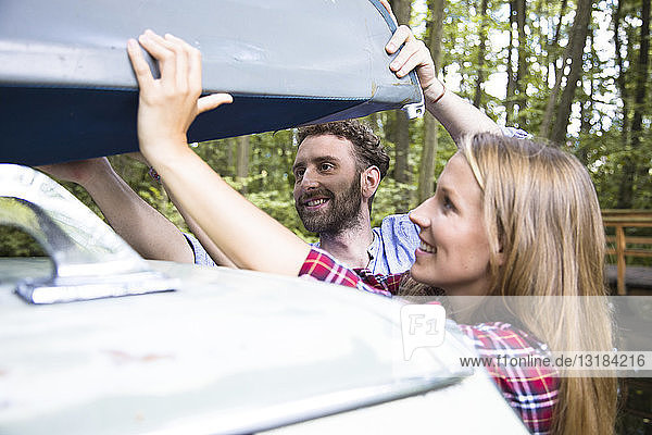 Smiling young couple taking canoe from car roof