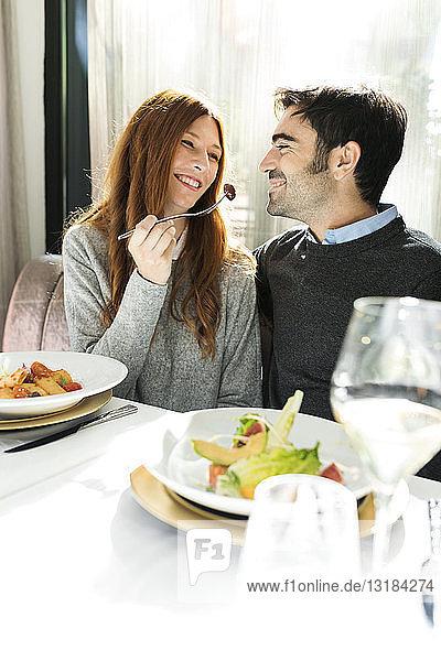 Lächelnde Frau lässt in einem Restaurant den Mann das Essen kosten