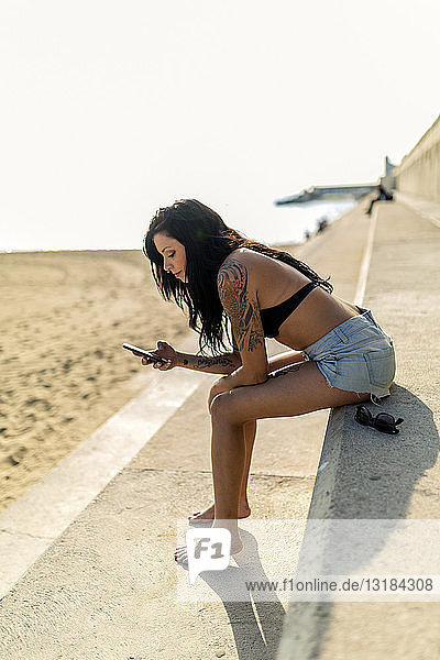 Smiling young woman with nose piercing and tattoos using smartphone near the beach