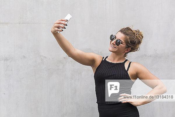 Porträt einer lächelnden  schwarz gekleideten jungen Frau  die sich mit einem Smartphone selbstständig macht