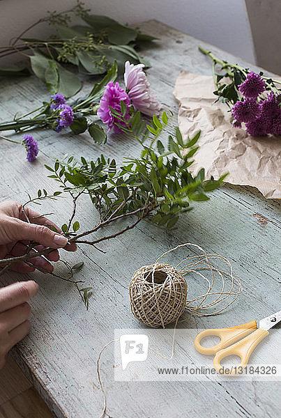 Frau bindet Blumenstrauss von Hand