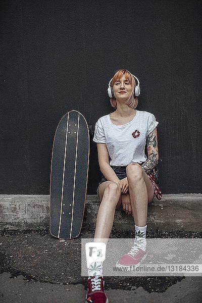 Lächelnde junge Frau mit Skateboard und Kopfhörern sitzt und hört Musik