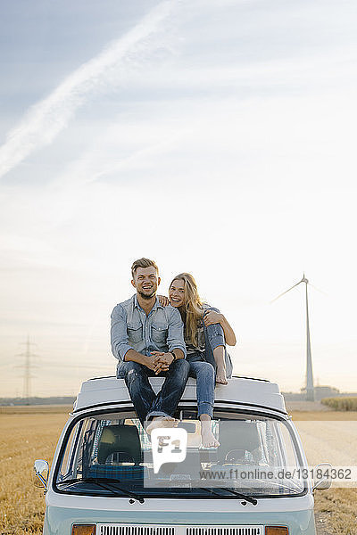 Porträt eines glücklichen jungen Paares auf dem Dach eines Wohnmobils in ländlicher Landschaft