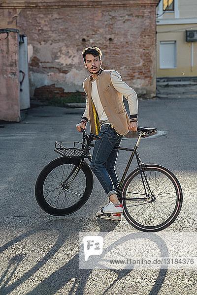 Junger Mann mit Pendler-Fixie-Fahrrad auf einem Hinterhof in der Stadt