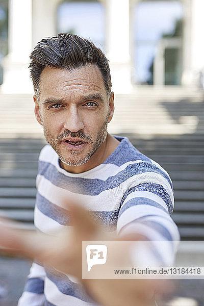 Porträt eines reifen Mannes  der seine Hand hebt