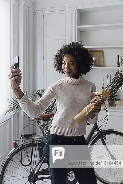 Mittlere erwachsene Freiberuflerin  die in ihrem Home-Office steht und ein Selfie