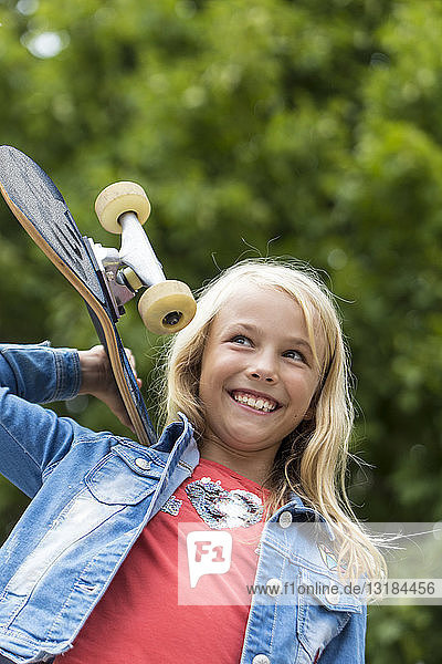 Portrait of happy blond girl with skateboard on her shoulder