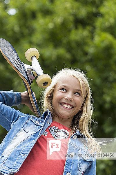 Portrait of happy blond girl with skateboard on her shoulder