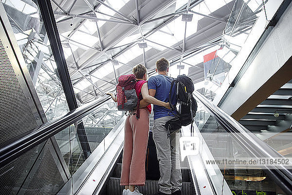 Rear view of couple on escalator at the airport