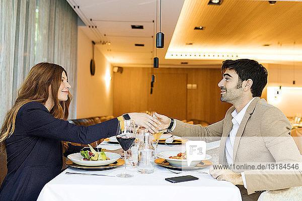 Lächelnder Mann und Frau beim Händeschütteln in einem Restaurant