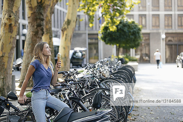 Niederlande  Maastricht  lächelnde blonde junge Frau  die in der Stadt am Fahrradständer eine Eistüte hält