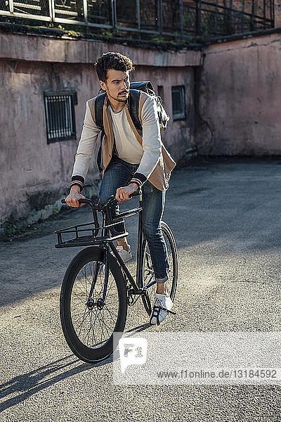 Junger Mann mit Rucksack fährt Pendler-Fixie-Fahrrad in der Stadt