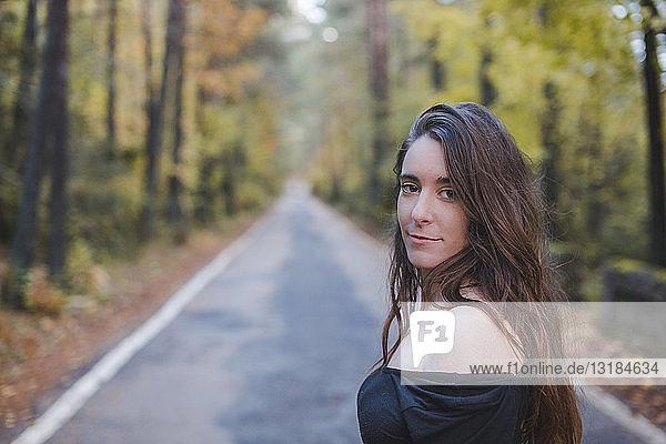 Porträt einer lächelnden jungen Frau auf der Landstraße