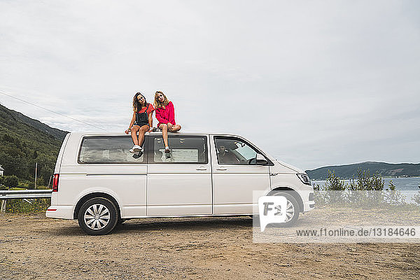 Friends traveling through Norwegian lapland with a camping van