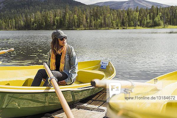 Finnland  Lappland  Frau sitzt in einem Boot auf einem See