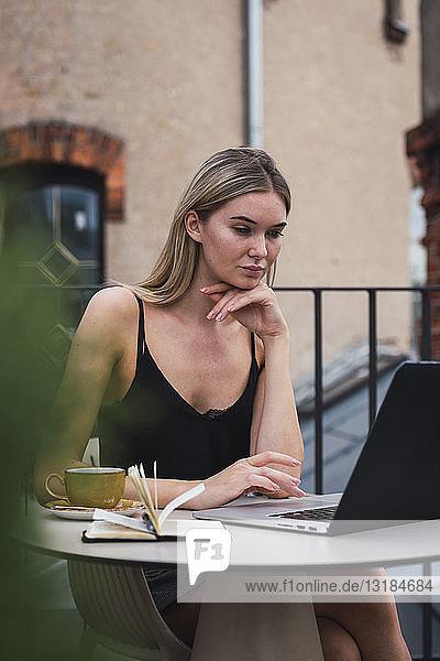 Porträt einer jungen Frau  die mit einem Laptop auf der Dachterrasse sitzt