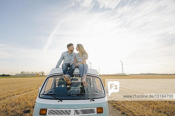 Lächelndes junges Paar auf dem Dach eines Wohnmobils in ländlicher Landschaft