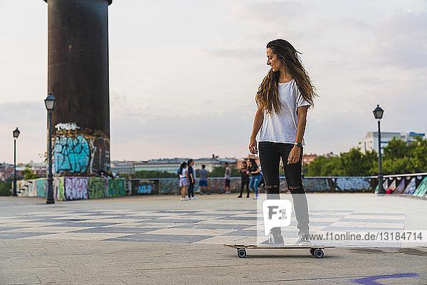 Junge Frau fährt Skateboard in der Stadt