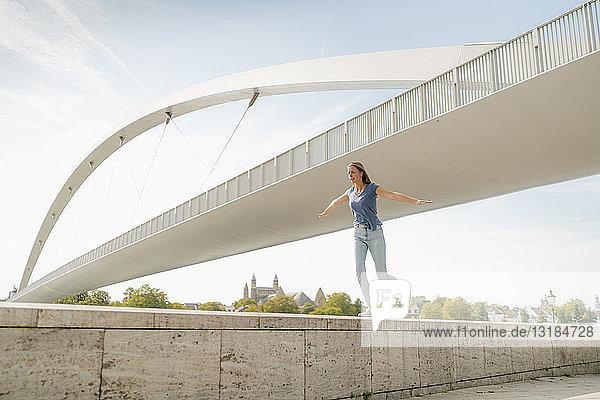 Niederlande  Maastricht  junge Frau balanciert auf einer Mauer an einer Brücke