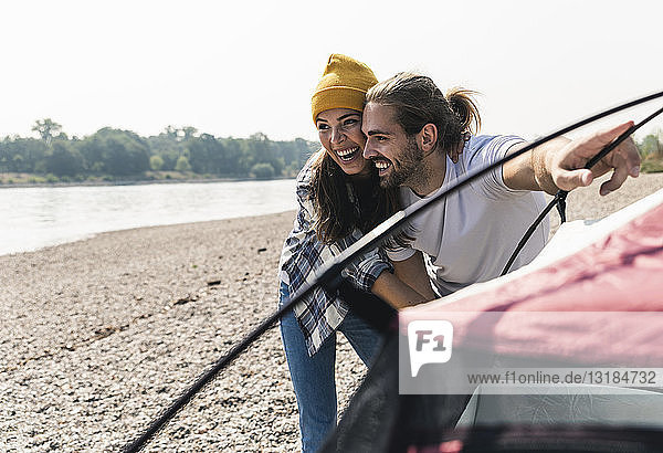 Happy young couple setting up a tent at the riverside