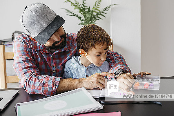 Father texplaining his son the smartwatch  while working at home