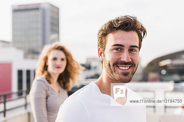 Porträt eines glücklichen jungen Mannes mit Freundin im Hintergrund bei Sonnenuntergang