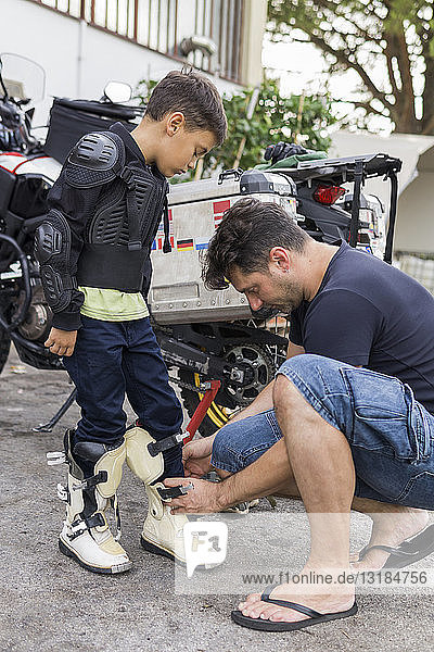 Father preparing son for a motorbike trip
