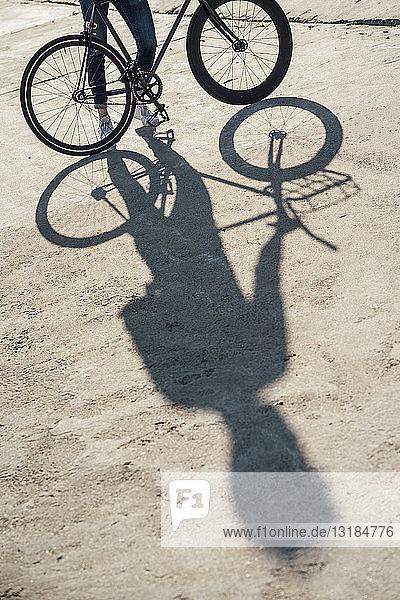 Nahaufnahme eines Mannes mit Pendler-Fixie-Fahrrad auf Betonplatte
