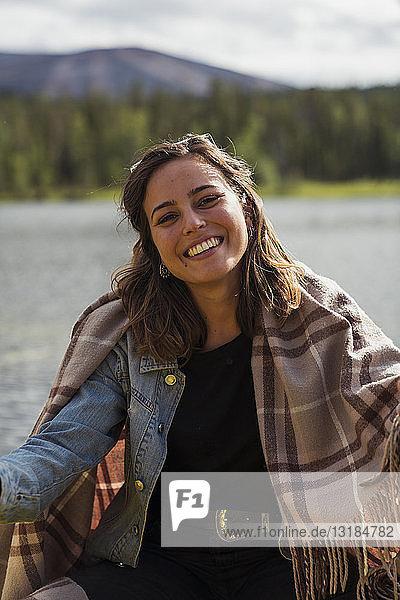 Finnland  Lappland  Porträt einer lächelnden jungen Frau mit einer Decke in einem Boot auf einem See