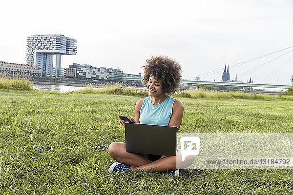 Deutschland  Köln  Frau sitzt mit Laptop und Handy auf der Wiese
