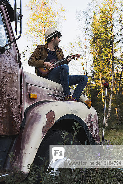 Young amn sitting on a broken truck  playing the ukulele