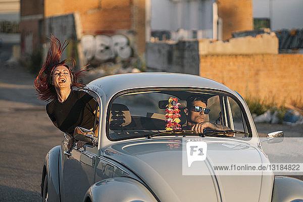 Ehepaar fährt in einem Oldtimer  Frau bindet sich aus dem Fenster