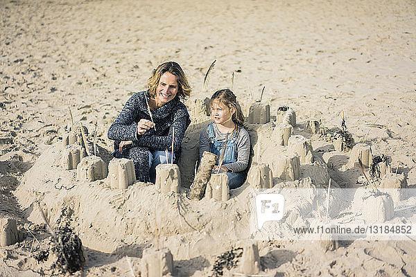 Mutter und Tochter bauen eine Sandburg am Strand