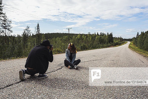 Finland,  Lapland,  man taking picture of woman sitting on empty country road