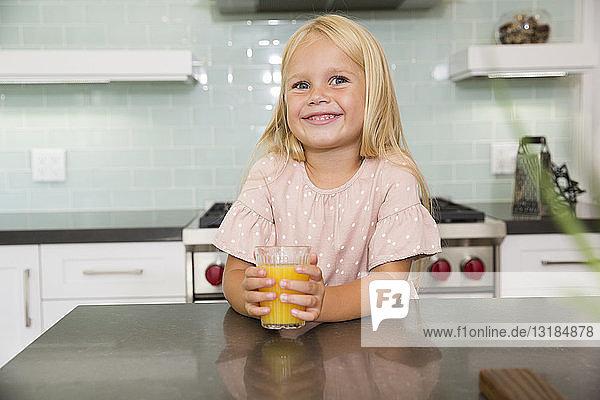 Porträt eines lächelnden Mädchens in der Küche mit einem Glas Orangensaft