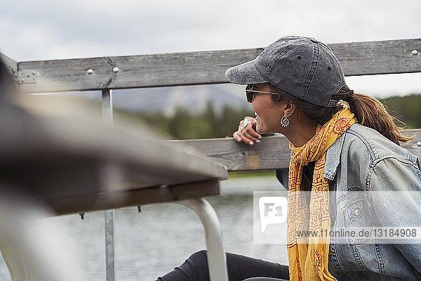 Finnland  Lappland  lächelnde junge Frau auf dem Steg am See
