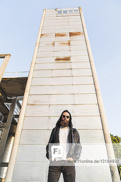 Cool bearded young man wearing sunglasses and hooded jacket standing in front of a tower