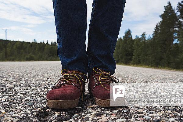 Finnland  Lappland  Menschenfüße stehen auf leerer Landstraße