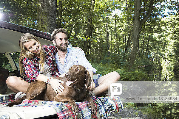 Smiling young couple with dog sitting in car at a brook in forest