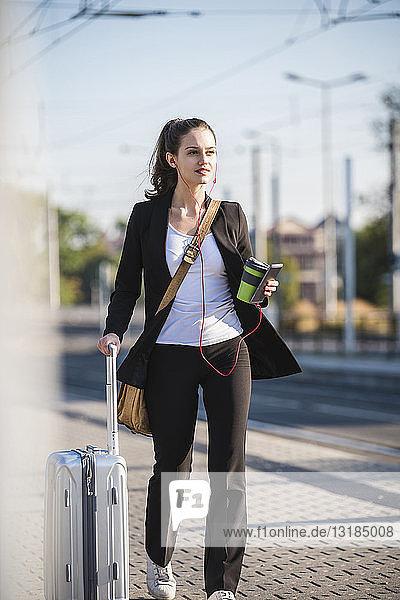 Junge Frau mit Gepäck in der Stadt unterwegs