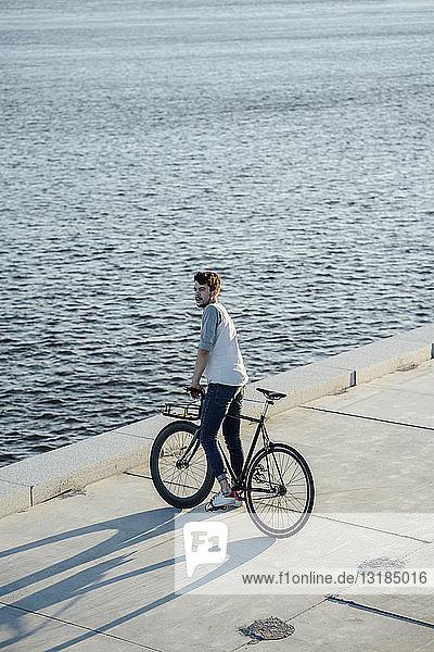Junger Mann mit Pendler-Fixie-Fahrrad bei einer Pause am Flussufer
